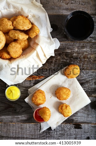 Top view of crispy breaded golden chicken nuggets on parchment paper. Ketchup and mustard bowls near it. Textured wood background, Bowl with nuggets and glass of cola on backside - stock photo