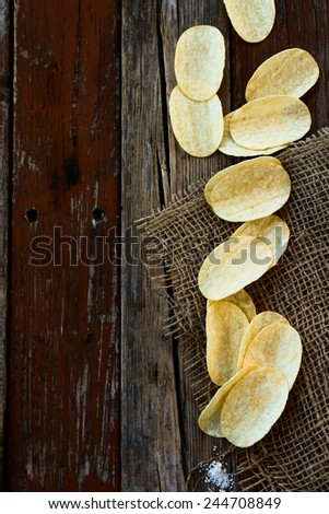 Top view of Crispy potato chips on jute and wooden texture. - stock photo