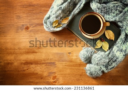 Top view of Cup of black coffee with autumn leaves, a warm scarf and old book on wooden background - stock photo