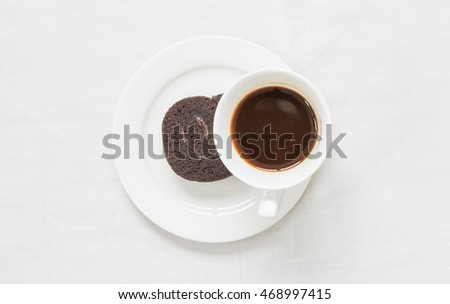 Top view of cup of coffee and chocolate cake on white tableclothes background.