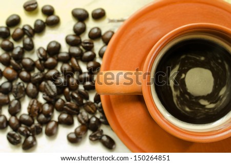 Top view of cup of coffee and coffee beans on wooden table,selective focus. - stock photo