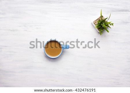 Top view of cup of coffee on a white wooden table. Break from work, lifestyle concept.  - stock photo