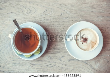 Top view of cup of tea and cup of coffee on the wooden table  - stock photo