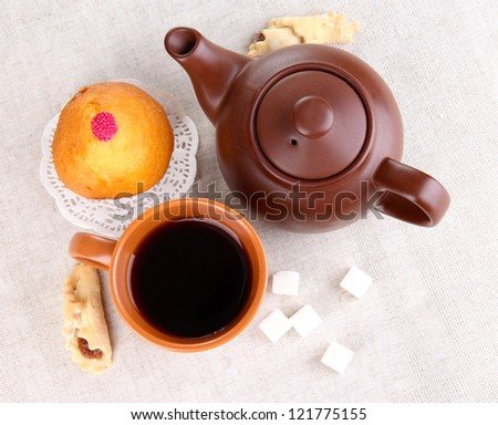 Top view of cup of tea and teapot on linen tablecloths