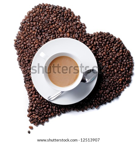 Top view of cup with heart shaped coffee beans in the background