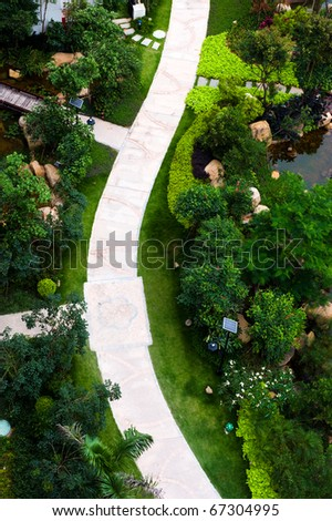 top view of curve brick path in garden, and surrounded by green plants. - stock photo