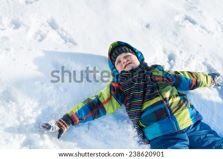 Top view of cute boy lying on snow - stock photo