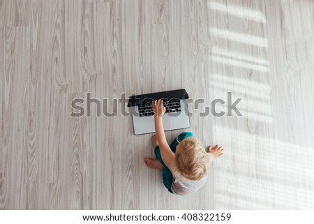 Top view of cute child using laptop at home with copy space - stock photo