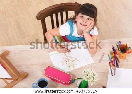 Top view of cute little girl drawing picture with multicoloured pencils while sitting at table at home. Pretty lady dreaming and looking at camera. - stock photo