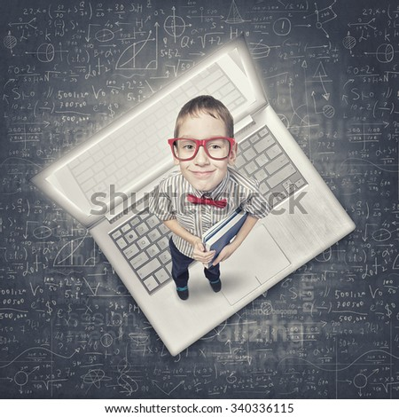 Top view of cute schoolboy in red glasses on chalkboard background - stock photo