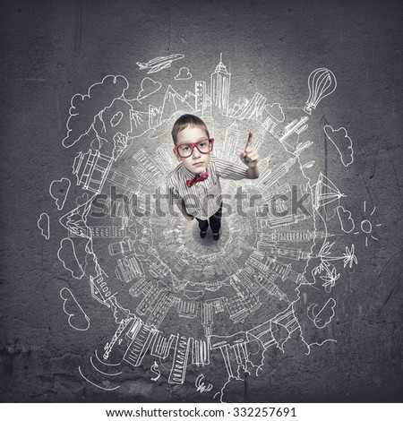 Top view of cute schoolboy in red glasses with books in hand - stock photo