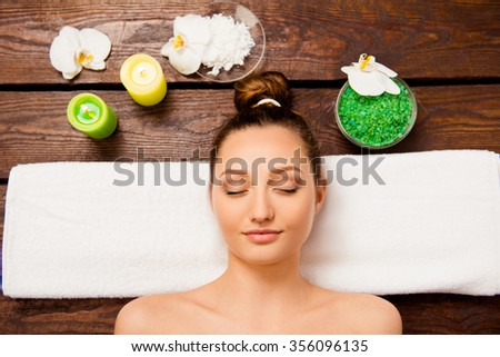 Top view of cute young woman laying in spa salon relaxing with closed eyes - stock photo
