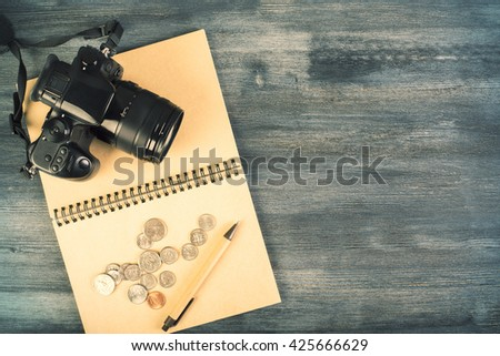 Top view of dark wooden desktop with camera, coins and pen on open spiral notepad. Mock up - stock photo