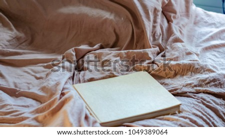 Top View Of Dark Wrinkled Bed Sheets And Book Messed Up After Nights Sleep.  Insomnia