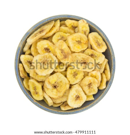 Top view of dehydrated banana chips in an old stoneware bowl isolated on a white background.