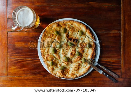Top view of delicious Aglio Olio Pizza and Beer Mug on wooden table. Ingredients marinade of olive oil, garlic, basil, oregano, olives. - stock photo