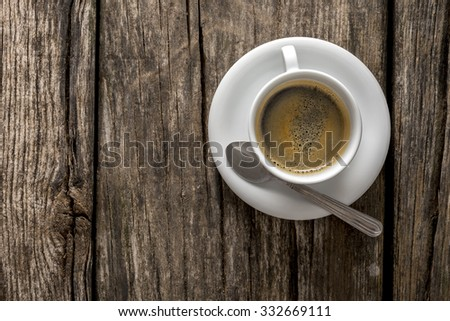 Top view of delicious hot freshly served cup of black Arabic coffee on a textured rustic wooden desk. Wit copy space on the left side. - stock photo