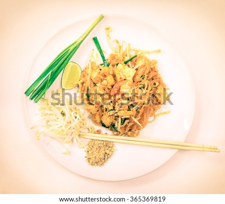 Top view of delicious Pad Thai served with lime on decorated plate with soy bean sprouts and peanuts - Traditional asian food with rice noodles and shrimps - Vintage filtered look with vignetting - stock photo