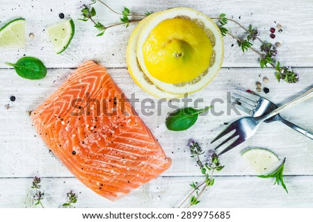 Top view of delicious portion of raw salmon fillet with aromatic herbs, spices and lemon. Vegetarian or paleo food concept. 