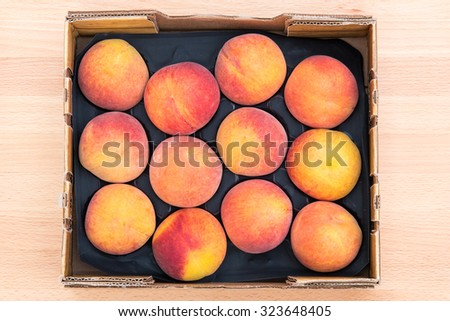 Top view of delicious red yellow peaches in a cardboard box. - stock photo