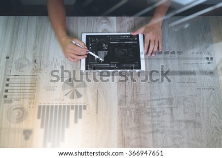 top view of Designer hand working with digital tablet computer with design diagram layer effect on wooden desk as responsive web design concept - stock photo