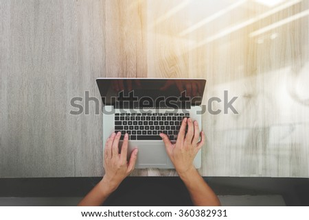 top view of Designer hand working with laptop computer on wooden desk as responsive web design concept - stock photo