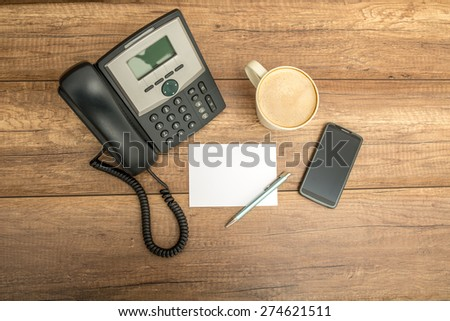 Top view of desk phone, blank note paper, pen, a cup of coffee and a smart phone, on a wooden table with copyspace. - stock photo