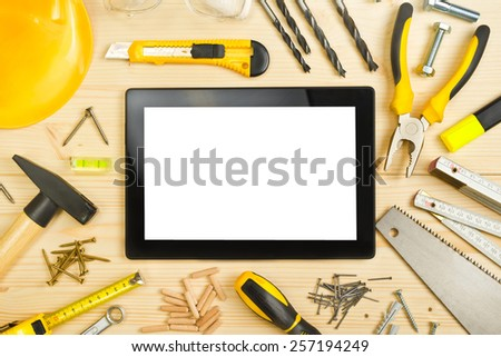 Top View of Digital Tablet and Assorted Woodwork and Carpentry Tools  on Pinewood Workshop Table - stock photo