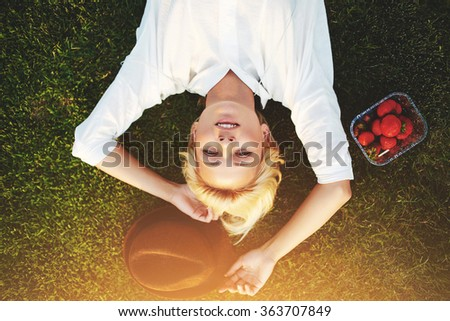 Top view of dreamy young hipster girl relaxing in the meadow during recreation time in sunny day, beautiful woman enjoying summer sunlight while lying on green grass after eating strawberries - stock photo