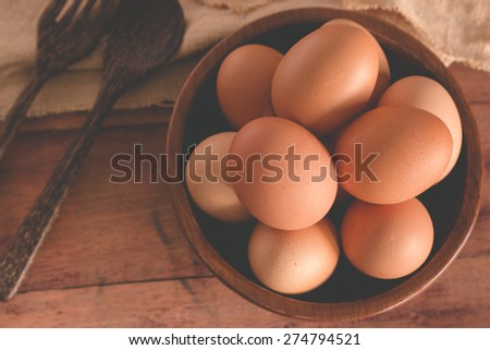 top view of eggs in wooden bowl with wooden Spoon and fork on wood table - stock photo