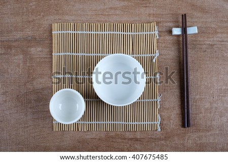 Top view of empty ceramic bowl, cup and chopstick on wooden textured background, flat lay.