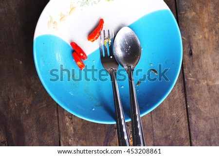 Top view of empty dish after finished meal, sliced chilli left on plate on wooden background. - stock photo