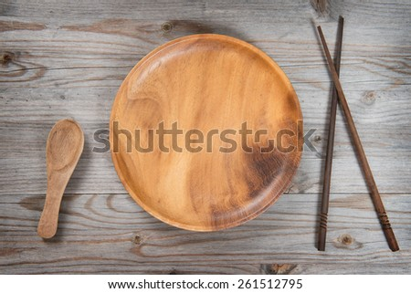 Top view of empty plate and sushi chopsticks on old wooden table. Dramatic light. - stock photo