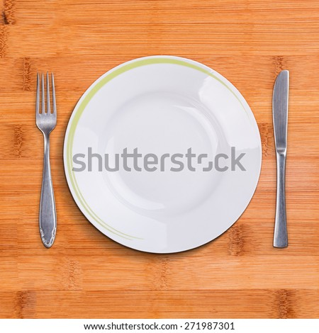 Top view of empty plate, fork and table knife on wooden background