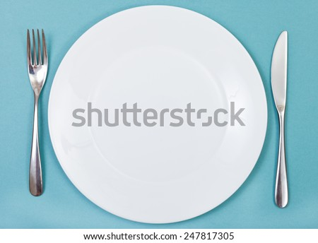 top view of empty white porcelain plate with fork and knife set on green background - stock photo