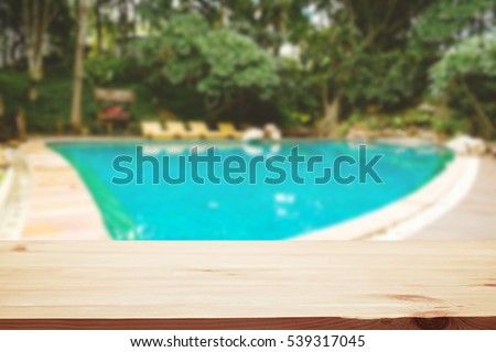 Top View Of Empty Wood Table Space Over Swimming Pool Background. For  Product Display Montage