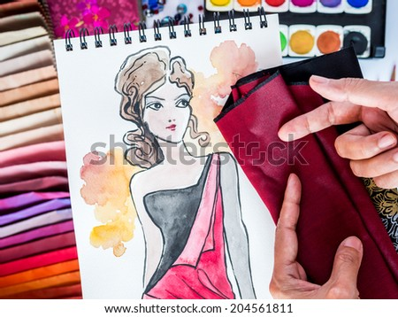 Top view of fashion designer working with material sample and hand-drawn illustration