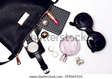Top view of female accessories for woman. Fancy sunglasses, leather bag , watch , lipstick , perfume , rings , mobile phone - stock photo