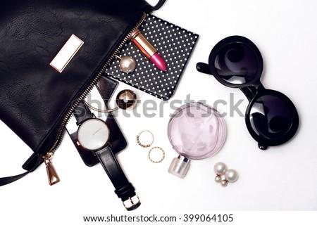 Top view of female accessories for woman. Trendy black sunglasses, black handbag , watch , lipstick , perfume , rings , smart phone - stock photo