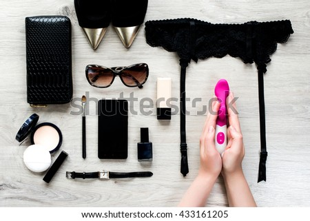 Top view of female fashion accessories for woman. Sex toy in the hands, sunglasses, face powder, make up brush, nail polish, watch, mobile phone, lipstick, gold pointed shoes, purse - stock photo