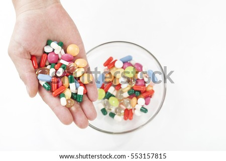Top view of female hands holding different pills