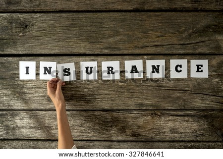 Top view of female insurance agent assembling the word Insurance with white cards with letters on them over a rustic textured wooden desk. - stock photo