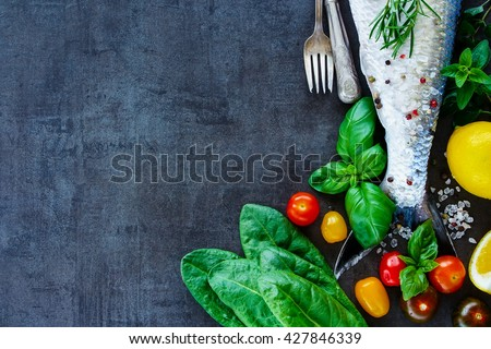 Top view of fish dishes cooking background with space for text. Fresh fish with various ingredients on dark vintage board, preparation. Flat lay. Healthy food or diet nutrition concept. - stock photo