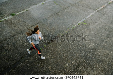 Top view of fit female athletes running on rainy day. Woman exercising outdoor on urban asphalt. - stock photo