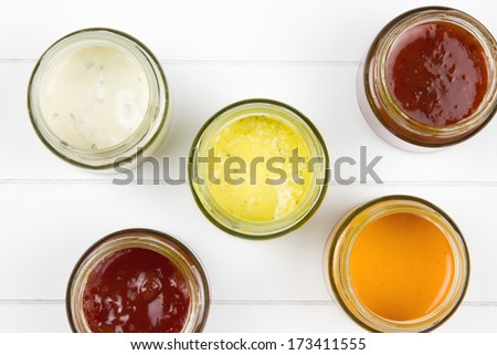top-view of five jars filled with curry sauce, tomato sauce, garlic sauce, salsa sauce and whiskey sauce on a wooden surface - stock photo