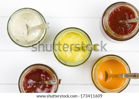 top-view of five jars filled with curry sauce, tomato sauce, garlic sauce, salsa sauce and whiskey sauce with spoons in it on a wooden surface  - stock photo