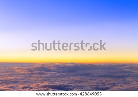 Top view of fluffy cloud flying on sunset sky view from flying airplane - stock photo