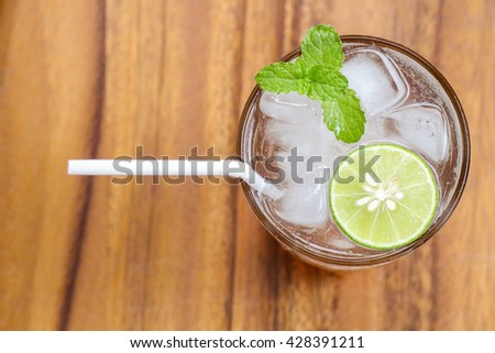 Top view of fresh cocktail with lime slice and mint on wood background. Mojito cocktail. Virgin mojito. Non-alcoholic mojito mocktail. Margarita cocktail. Fresh lemonade. Honey lemon soda. - stock photo