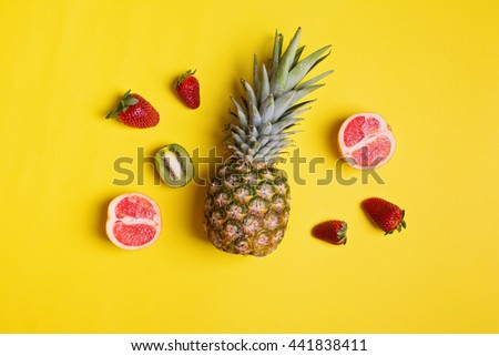 Top view of fresh fruits on yellow background. Overhead concept shot of pineapple, strawberries, sliced kiwi and grapefruit. No retouch, no filter. - stock photo