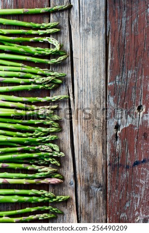 Top view of fresh green asparagus on rustic wooden texture. Food background. - stock photo